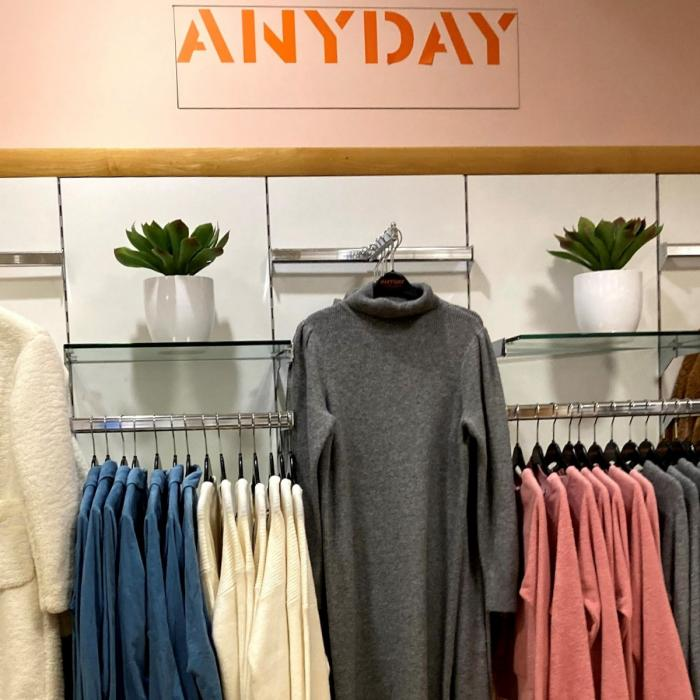 A modern retail space with plants and clothes hanging on a peach coloured wall