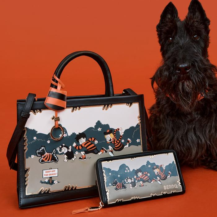 Black scottie dog sitting with two Beano themed bags on a red backdrop